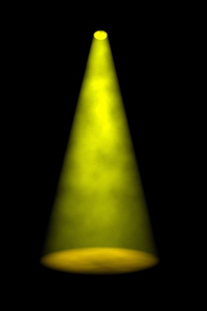 beams: Single yellow smoky spotlight beam shining directly down onto an empty stage against a dark background