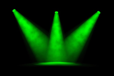 Three wide green foggy spotlight beams converging to a central spot on an empty stage against a black background photo