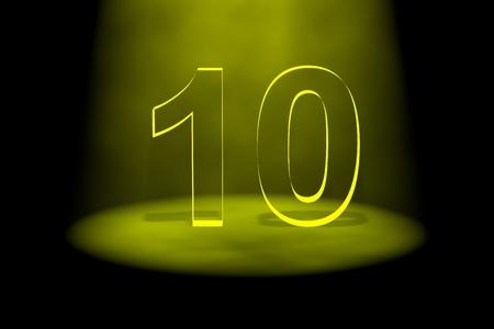 spotlit: Number 10 illuminated with yellow light on black background