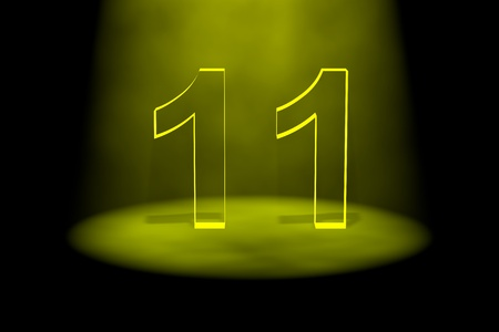 11 number: Number 11 illuminated with yellow light on black background
