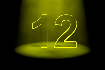 number 12: Number 12 illuminated with yellow light on black background Stock Photo