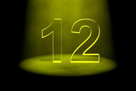 spotlit: Number 12 illuminated with yellow light on black background Stock Photo