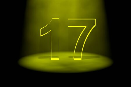 17: Number 17 illuminated with yellow light on black background