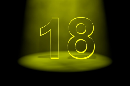 spotlit: Number 18 illuminated with yellow light on black background Stock Photo
