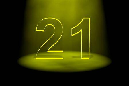Number 21 illuminated with yellow light on black background photo