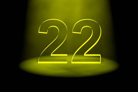Number 22 illuminated with yellow light on black background Stock Photo - 13588616