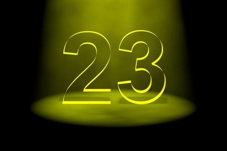 Number 23 illuminated with yellow light on black background photo