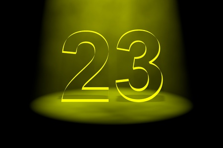 spotlit: Number 23 illuminated with yellow light on black background Stock Photo
