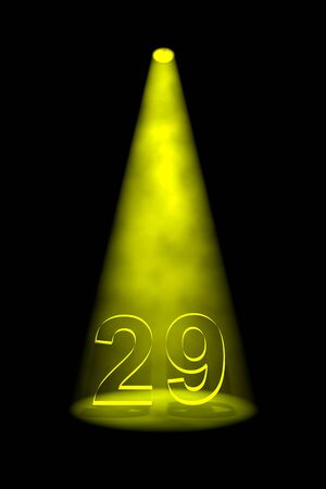 spotlit: Number 29 illuminated with yellow spotlight on black background Stock Photo