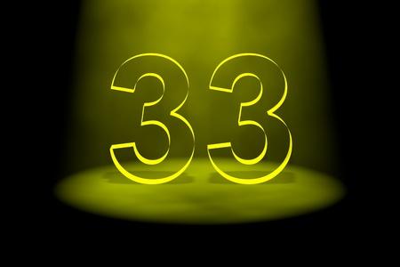 Number 33 illuminated with yellow light on black background photo