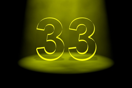 spotlit: Number 33 illuminated with yellow light on black background