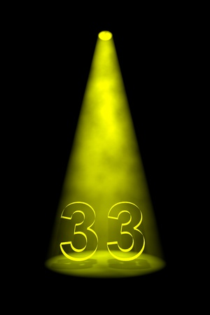 spotlit: Number 33 illuminated with yellow spotlight on black background Stock Photo