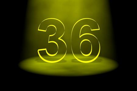36: Number 36 illuminated with yellow light on black background