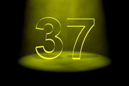 Number 37 illuminated with yellow light on black background photo