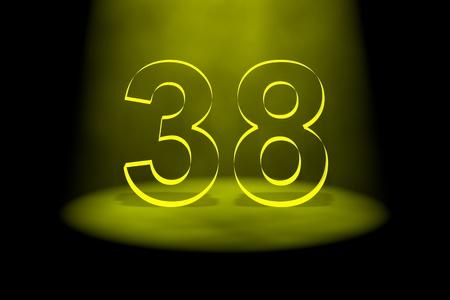 Number 38 illuminated with yellow light on black background photo