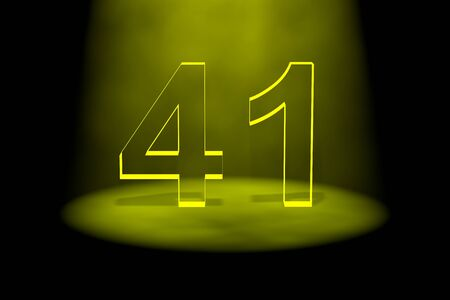 spotlit: Number 41 illuminated with yellow light on black background Stock Photo