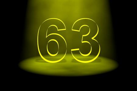 spotlit: Number 63 illuminated with yellow light on black background