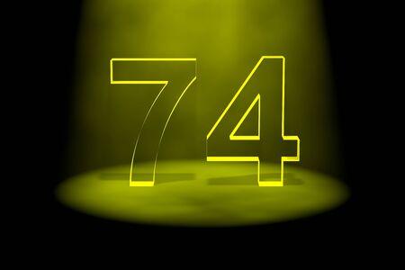 Number 74 illuminated with yellow light on black background photo