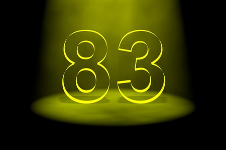 Number 83 illuminated with yellow light on black background photo