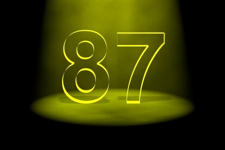 spotlit: Number 87 illuminated with yellow light on black background Stock Photo