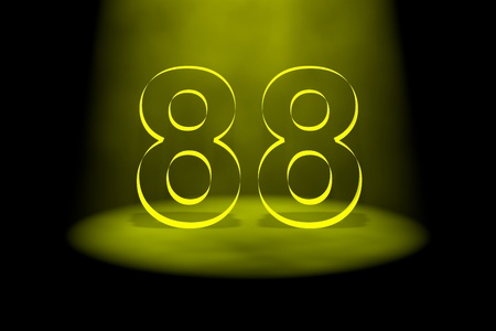 spotlit: Number 88 illuminated with yellow light on black background Stock Photo