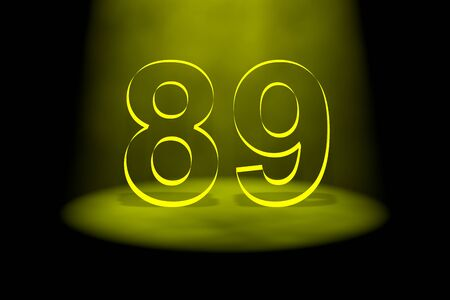 spotlit: Number 89 illuminated with yellow light on black background Stock Photo