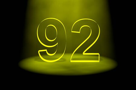Number 92 illuminated with yellow light on black background photo