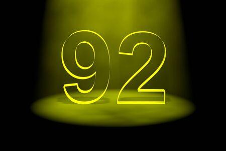 spotlit: Number 92 illuminated with yellow light on black background