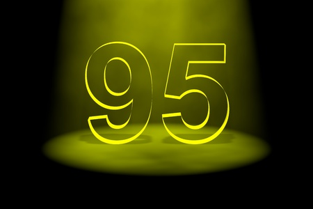 spotlit: Number 95 illuminated with yellow light on black background Stock Photo