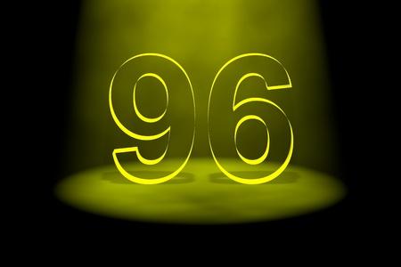 Number 96 illuminated with yellow light on black background photo