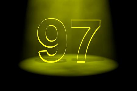 Number 97 illuminated with yellow light on black background photo