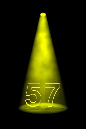 Number 57 illuminated with yellow spotlight on black background Stock Photo - 13588585
