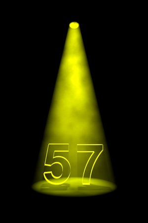 limelight: Number 57 illuminated with yellow spotlight on black background Stock Photo