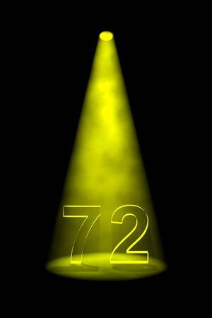 spotlit: Number 72 illuminated with yellow spotlight on black background Stock Photo