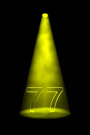 Number 77 illuminated with yellow spotlight on black background Stock Photo - 13588579