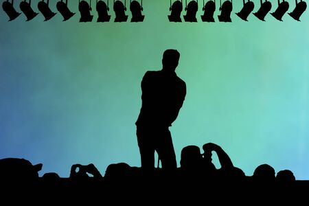 adoring: Silhouette of a live performer on stage in a smoky auditorium with a row of spotlights and an adoring audience