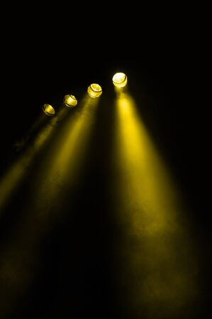diverging: Four diverging spotlights with yellow beams in a receding line shining at night in a foggy environment