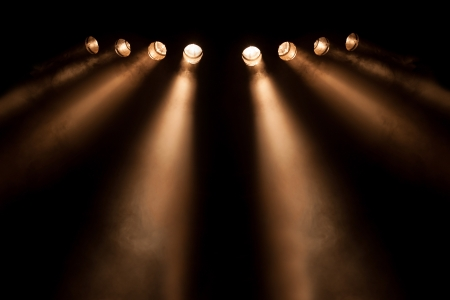 Stage lighting: A line of eight divergent directional spotlight beams shining at night , symmetrically arranged with perspective