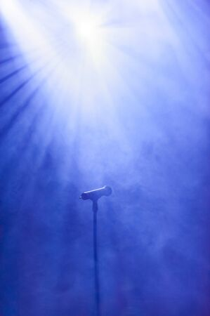 openair: Microphone lit by a floodlight against a smoky blue sky ready for a vocalist or speaker at an open-air concert or rally