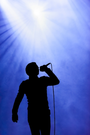 singer with microphone: Silhouette illustration of a man singing under a floodlight at an open-air concert against a hazy smoky blue sky