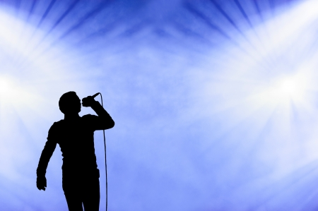 the vocalist: Silhouetted illistration of a male singer performing against a blue cloudy smoke filled sky at an open-air concert with floodlights