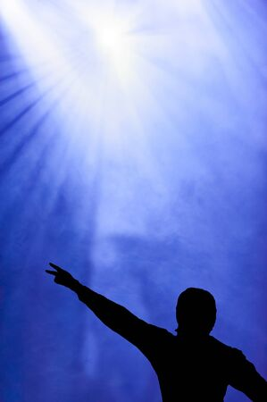 rally finger: Silhouetted illustration of a man giving the Victory sign against a blue hazy sky lit by a floodlight at an open-air festival or meeting Stock Photo