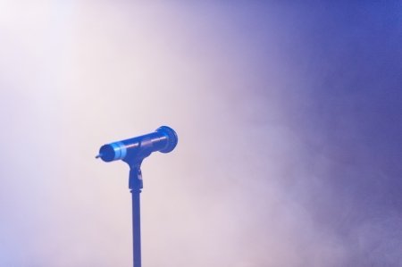unattended: Blue toned image of an unattended microphone on empty smoky background with copyspace Stock Photo