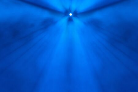 diverging: Single distant spotlight centred at the top of the frame shining downwards through foggy blue air with diverging beams of light Stock Photo