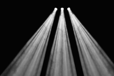 diverging: Three diverging spotlights or floodlights with powerful diverging beams shining at night