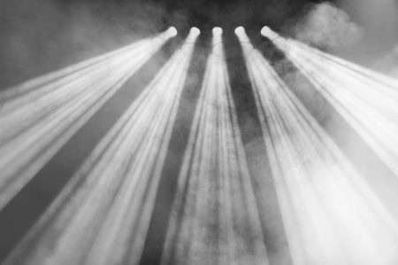 diverging: Five powerful spotlights with diverging beams shining down in a foggy atmosphere at a concert or function