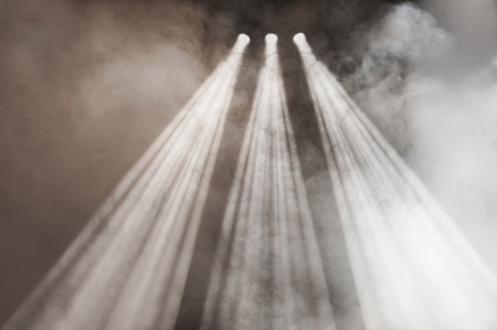 wafting: Three spotlights shining down with diverging beams in a smoke-filled atmosphere Stock Photo