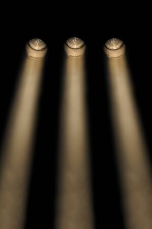 limelight: Three yellow divergent symmetrical spotlights in a smoky atmosphere in a line shining downwards at night