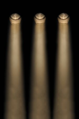 downwards: Three yellow symmetrical spotlights in a smoky atmosphere in a line shining downwards at night in an auditorium or concert Stock Photo