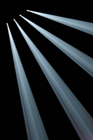 oblique: Background illustration of four obllique spotlights in a row in the top left corner with indiviual white beams shining in smoky darkness Stock Photo